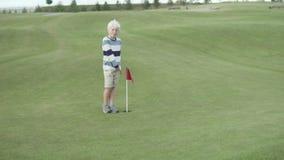 Un muchacho rubio está corriendo alrededor del campo de golf almacen de metraje de vídeo