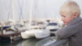 Un muchacho rubio triste se coloca en el embarcadero cerca de los yates y miradas en el mar almacen de video