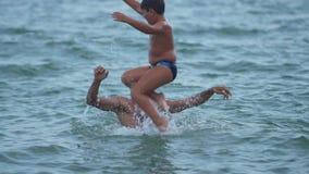 Un muchacho salta en el agua con su vídeo de la cámara lenta de los hombros del ` s del padre metrajes