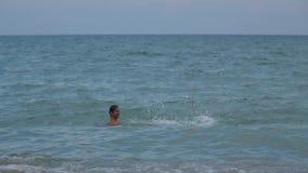 Un muchacho salta en el agua de su vídeo de la cámara lenta de los hombros del ` s del padre almacen de video