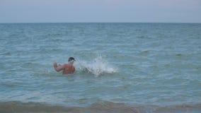 Un muchacho salta en el agua de su vídeo de la cámara lenta de los hombros del ` s del padre metrajes
