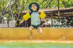 Un muchacho salta en el agua en una piscina Imagen de archivo