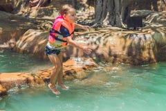 Un muchacho salta en el agua en una piscina Fotografía de archivo libre de regalías
