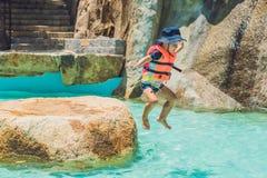 Un muchacho salta en el agua en una piscina Foto de archivo libre de regalías