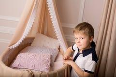 Un muchacho se coloca cerca de la cuna Foto de archivo libre de regalías