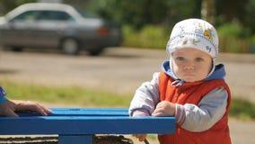 Un muchacho se coloca cerca del banco en el patio con la expresión honesta El muchacho es menos que un año, un chaleco rojo y a almacen de metraje de vídeo