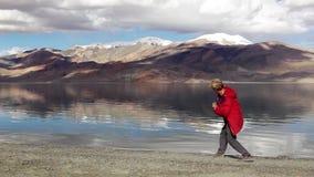 Un muchacho se coloca cerca del lago de la alto-montaña y salta piedras almacen de metraje de vídeo