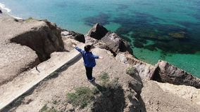 Un muchacho se coloca de extensión de sus brazos en la costa que el sol brilla en su cara el viento almacen de metraje de vídeo