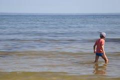 Un muchacho se está colocando en el mar Báltico fotos de archivo