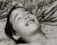 Un muchacho se relaja en la playa Fotografía de archivo