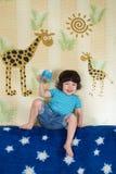 Un muchacho se sienta en el sofá en el cuarto y la bebida Foto de archivo libre de regalías