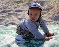 Un muchacho se sienta en la arena Foto de archivo libre de regalías