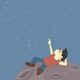 Un muchacho se sienta en la superficie de la luna y explora las constelaciones en el cielo (extranjero o apenas un sueño) imagen de archivo