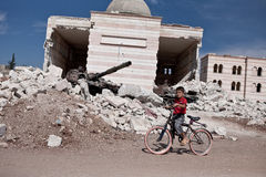 Un muchacho sirio en la bici afuera de la mezquita dañada en Azaz, Siria. Fotografía de archivo libre de regalías