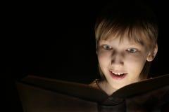 Un muchacho soñador hermoso con un libro Foto de archivo libre de regalías