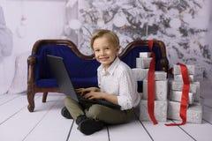 Un muchacho sonriente como Santa Claus con un árbol de navidad en el fondo fotos de archivo
