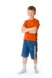 Un muchacho sonriente con sus manos cruzadas Imagenes de archivo