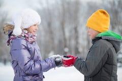 Un muchacho sonriente con una muchacha en parque del invierno Fotos de archivo libres de regalías