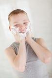 Un muchacho sonriente que hace espuma su cara con ambas manos Imagenes de archivo