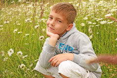 Un muchacho sonriente rodilla-doblado Fotos de archivo libres de regalías