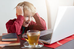 Un muchacho sorprendido del liitle con el pelo ligero se vistió en la camisa roja que se sentaba en la tabla y las historietas o  Fotografía de archivo libre de regalías