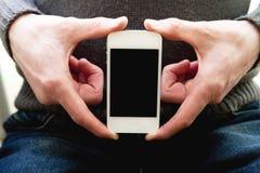 Un muchacho sostiene un smartphone disponible Foto de archivo libre de regalías