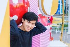 Un muchacho tailandés que se sienta en la pila de caja de la Navidad en Hua Hin Thai Foto de archivo libre de regalías