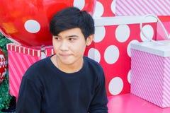 Un muchacho tailandés que se sienta en la pila de caja de la Navidad en Hua Hin Thai Fotografía de archivo libre de regalías