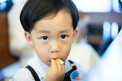 Un muchacho travieso come secretamente el caramelo, él está jugando en la iglesia foto de archivo