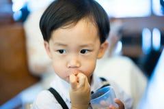 Un muchacho travieso come secretamente el caramelo, él está jugando en la iglesia imagenes de archivo