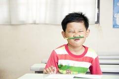 Un muchacho travieso en sala de clase Foto de archivo