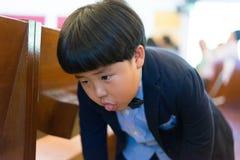 Un muchacho travieso hace la cara divertida, él está jugando en la iglesia fotos de archivo libres de regalías