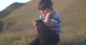 Un muchacho utiliza un teléfono móvil mientras que se sienta en una roca en la naturaleza almacen de video
