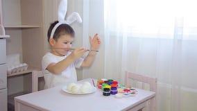 Un muchacho vestido como liebre pinta un huevo de Pascua HD 1920x1080 almacen de metraje de vídeo