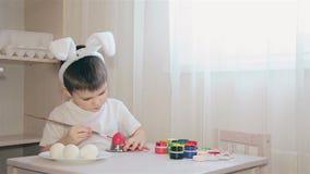 Un muchacho vestido como liebre pinta un huevo de Pascua Semana Santa holiday Huevo blanco 1080 HD almacen de metraje de vídeo