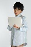 Un muchacho y su computadora portátil Fotos de archivo