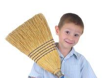 Un muchacho y su escoba Foto de archivo libre de regalías