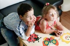 Un muchacho y su hermana están viendo la TV Imagen de archivo libre de regalías
