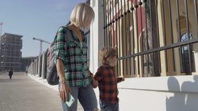 Un muchacho y su madre están caminando en la ciudad vieja Una mujer viaja con su hijo en lugares históricos almacen de metraje de vídeo