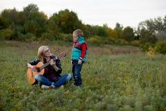 Un muchacho y su madre son que tocan y cantantes la guitarra en el autum Imagen de archivo libre de regalías