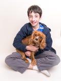 Un muchacho y su perro de perrito lindo Fotografía de archivo libre de regalías