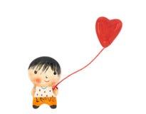 Un muchacho y un globo de la forma del corazón Imagenes de archivo