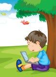 Un muchacho y una computadora portátil Imagen de archivo libre de regalías