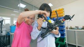 Un muchacho y una muchacha burlonamente están reparando un quadcopter almacen de video