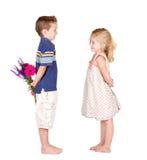 Un muchacho y una muchacha con las flores Foto de archivo libre de regalías