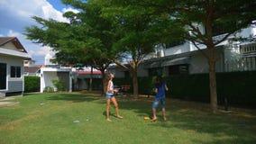 Un muchacho y una muchacha del adolescente juegan a bádminton en un césped verde en el patio trasero de su hogar foto de archivo