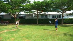 Un muchacho y una muchacha del adolescente juegan a bádminton en un césped verde en el patio trasero de su hogar imagen de archivo