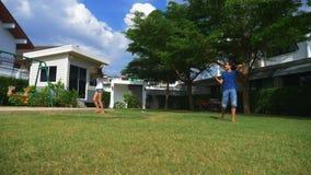 Un muchacho y una muchacha del adolescente juegan a bádminton en un césped verde en el patio trasero de su hogar fotos de archivo
