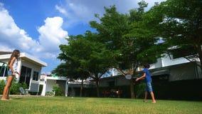 Un muchacho y una muchacha del adolescente juegan a bádminton en un césped verde en el patio trasero de su hogar fotografía de archivo libre de regalías