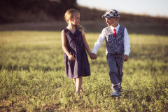 Un muchacho y una muchacha en el campo en la puesta del sol se encienden Imágenes de archivo libres de regalías